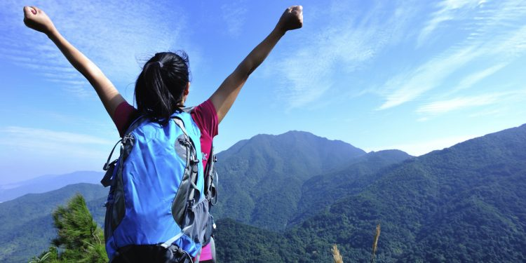 happy hiking woman raised arms at mountain peak