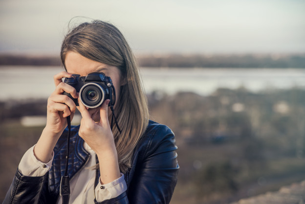 Portrait of a photographer covering her face with the camera.. Photographer woman girl is holding dslr camera taking photographs